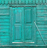 在装饰的墙壁上的老被绘的绿色木被关闭的窗口 库存图片