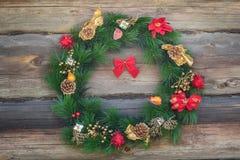 在老原木小屋墙壁背景的室外圣诞节针叶树花圈 免版税库存图片