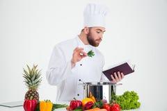 男性厨师厨师读书食谱书,当准备食物时 免版税库存照片