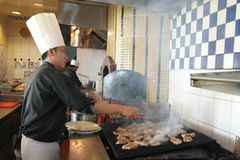 烹调牛排的主厨 免版税库存照片