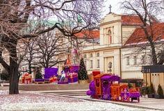 华沙著名老镇有教会、圣诞树、玩具火车和礼物的 波兰 免版税库存图片