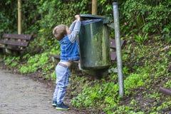 在容器的小男孩投掷的垃圾 免版税库存照片