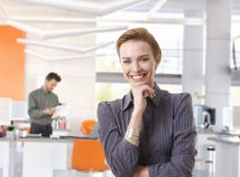 愉快的女实业家在现代办公室 免版税图库摄影