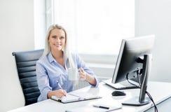工作在办公室的年轻,可爱和确信的女实业家 免版税库存图片