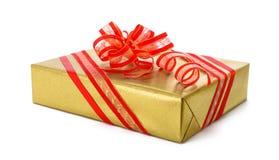 Απομονωμένο χρυσό κιβώτιο δώρων με το κόκκινο τόξο Στοκ φωτογραφία με δικαίωμα ελεύθερης χρήσης
