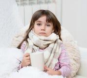 有一个杯子的病的哀伤的女孩在他的手上坐床 库存图片
