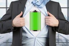 衣服的一个人撕毁蓝色衬衣 在胸口的充分的被充电的电池 库存图片