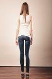 女孩全长在牛仔布长裤白色空白的顶端后方的视图 免版税库存图片