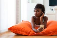 发在一个手机的非裔美国人的妇女一个正文消息 库存照片