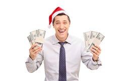 有拿着金钱的圣诞老人帽子的激动的人 免版税库存图片
