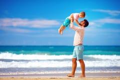 愉快的激动的获得父亲和的儿子在夏天海滩的乐趣,享有生活 免版税图库摄影