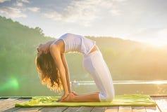 做在湖的妇女瑜伽-放松本质上 免版税图库摄影