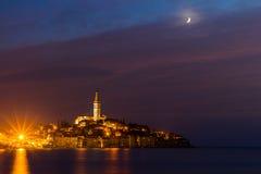 罗维尼老镇在与月亮在五颜六色的天空,克罗地亚,欧洲的亚得里亚海海岸的晚上 免版税图库摄影