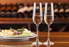 两杯与乳酪盘子的香槟  免版税图库摄影