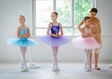 有个人芭蕾老师的三位小芭蕾舞女演员在舞蹈演播室 库存照片