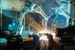 焊接机器人运动在汽车工厂 免版税库存照片