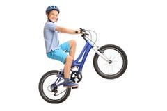 执行自行车前轮离地平衡特技的快乐的小男孩与他的自行车 免版税图库摄影
