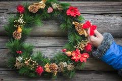 有装饰红色弓的人的胳膊在原木小屋墙壁有假日圣诞节花圈背景 免版税库存图片