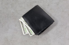 关闭美元金钱在桌上的黑钱包里 免版税图库摄影