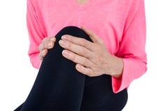 遭受膝盖痛苦的妇女的中间部分 库存照片