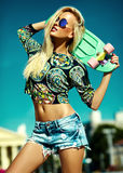 夏天行家的美丽的年轻白肤金发的式样女孩穿衣与滑板 库存照片