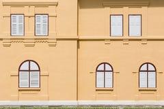在橙色大厦的闭合的白色木窗口 免版税库存照片