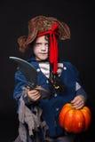 可爱的年轻男孩在海盗成套装备穿戴了,演奏把戏或款待为万圣夜 库存图片
