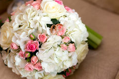 在红色和白玫瑰花束的两个婚戒  免版税库存图片