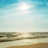 在剧烈的天空的太阳在海 免版税库存照片
