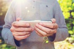 外面他的智能手机的年轻人 图库摄影