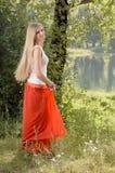 美好的年轻白肤金发的妇女跳舞在河岸的森林里 免版税库存图片