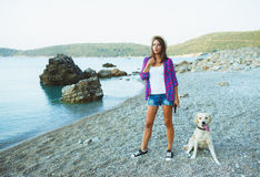 有一条狗的妇女在海滩的步行 免版税库存图片
