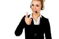 打手势耳机的呼叫中心查出好的白人妇女 免版税库存照片