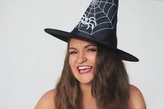 万圣夜巫婆帽子的滑稽的少妇 免版税库存照片