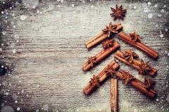 与圣诞节由香料肉桂条、茴香星和蔗糖做的杉树的圣诞卡在土气木背景 免版税库存照片