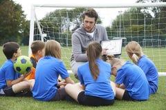 Тренер давая беседу команды к футбольной команде начальной школы Стоковые Фотографии RF