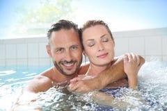 放松和享用在温泉的夫妇 免版税库存图片