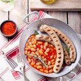 烤香肠用在西红柿酱的豆 免版税库存照片