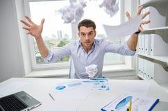 恼怒的商人投掷的纸在办公室 免版税库存照片