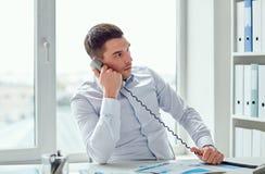 拜访电话的恼怒的商人在办公室 图库摄影