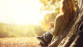 享用外带的咖啡杯的匿名妇女在晴朗的冷的秋天天 库存图片