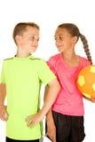 年轻拿着与态度的男孩和女孩一个足球 免版税库存图片