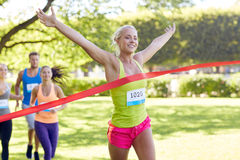 赢取在种族结束的愉快的年轻女性赛跑者 免版税库存图片