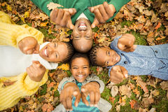 Η νέα οικογένεια που κάνει ένα κεφάλι περιβάλλει και που δείχνει τη κάμερα Στοκ Φωτογραφία