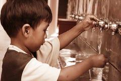 男孩新闻饮用水,葡萄酒口气 免版税库存图片