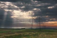 与高压导线的发行定向塔在日出 免版税库存照片