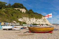 啤酒海滩德文郡有小船和英国旗子的英国英国圣乔治十字架侏罗纪海岸的 免版税库存照片