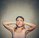 盖她的耳朵的不快乐的妇女查寻做喧闹声的中止 免版税库存照片