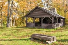 在秋叶中的原木小屋 免版税库存图片