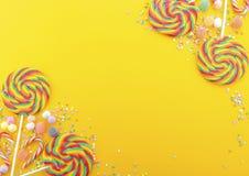 彩虹在明亮的黄色木桌上的棒棒糖糖果 图库摄影